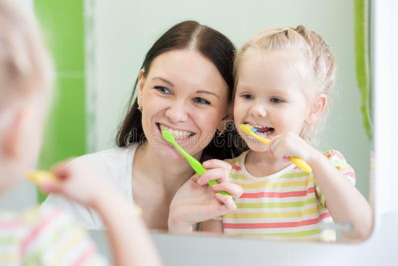 Δόντια βουρτσίσματος κορών μητέρων και παιδιών από κοινού στοκ εικόνες