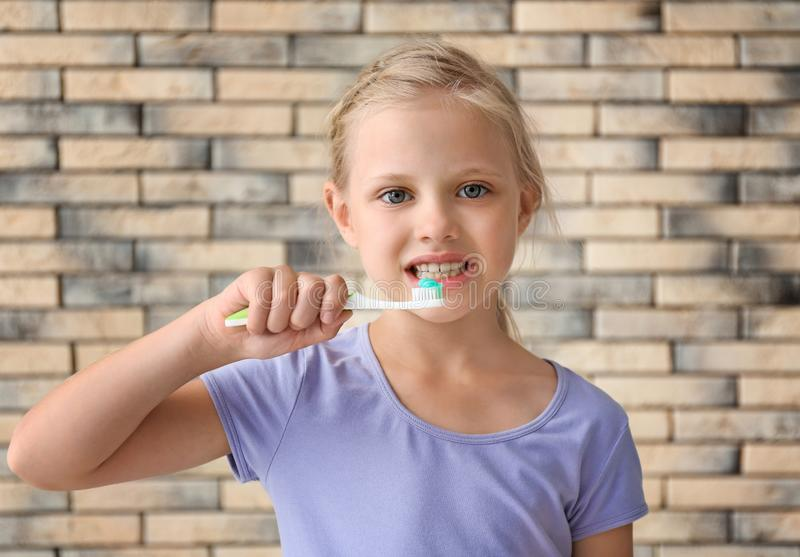 Δόντια βουρτσίσματος μικρών κοριτσιών ενάντια στο τουβλότοιχο στοκ εικόνες