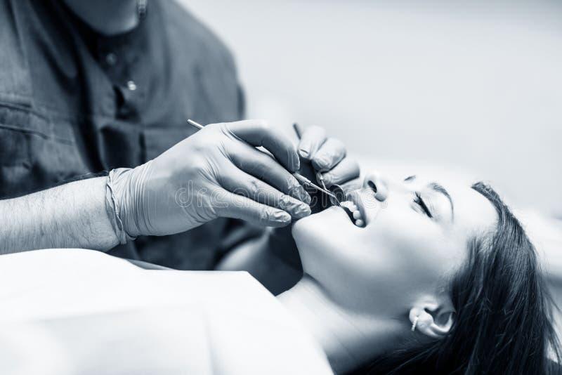 Δόντια εξέτασης οδοντιάτρων στο νέο ασθενή γυναικών στην κλινική στοκ φωτογραφία με δικαίωμα ελεύθερης χρήσης