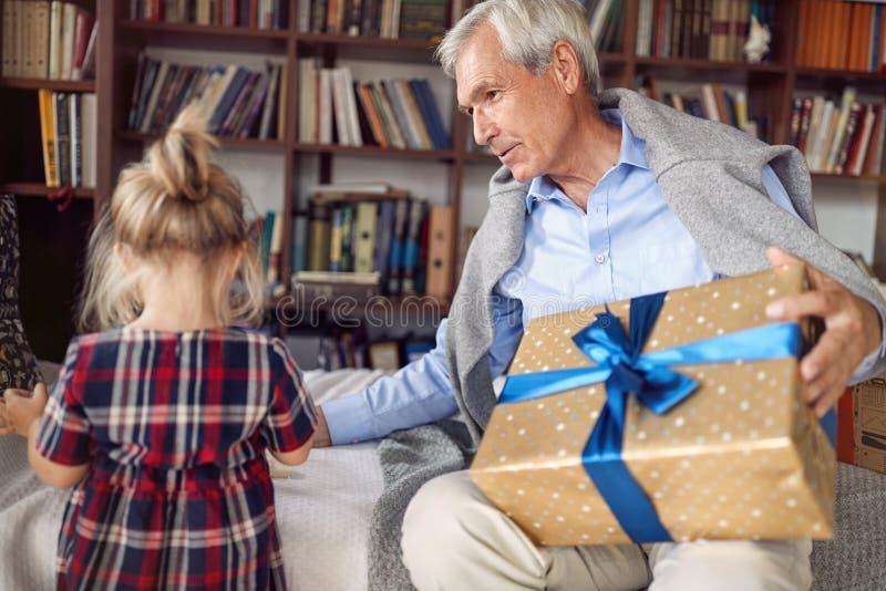 Δόσιμο του δώρου Χριστουγέννων στο χρονικό παππού εορτασμού με το δώρο για την εγγονή του στοκ εικόνα