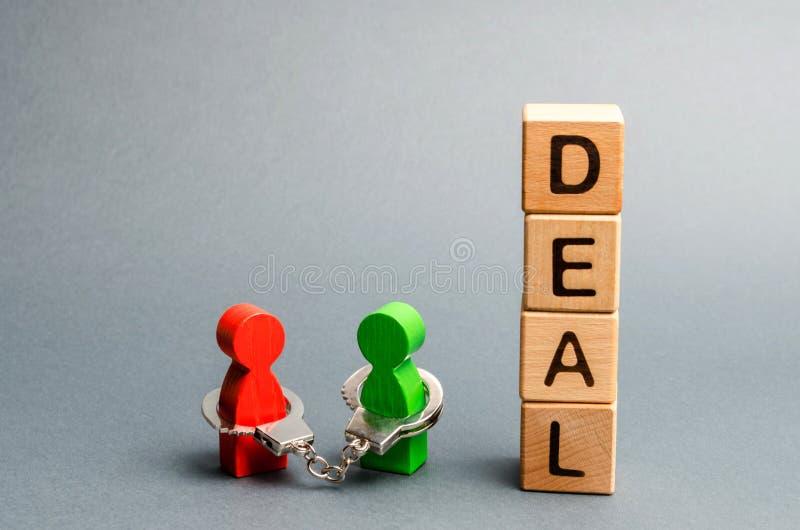 Δύο άνθρωποι είναι δεμένη με χειροπέδες ο ένας στον άλλο στάση κοντά σε μια διαπραγμάτευση λέξης Υποχρεώσεις Unclosed μεταξύ δύο  στοκ φωτογραφία