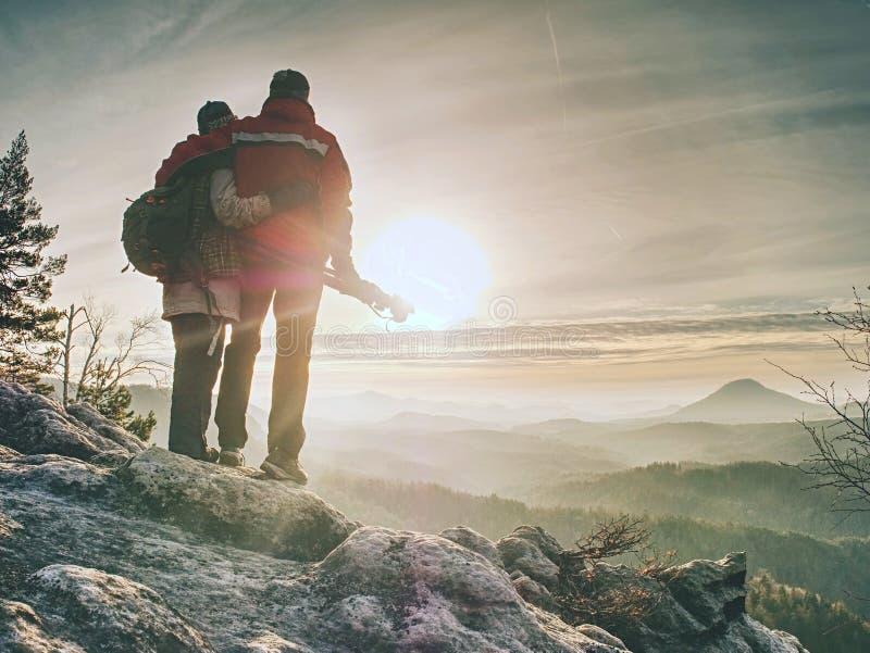 Δύο άνθρωποι μένουν στο τρίποδο στο υπόβαθρο μιας σειράς βουνών στοκ φωτογραφία
