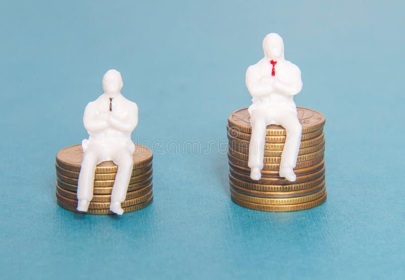 Δύο άνθρωποι παιχνιδιών κάθονται στην έννοια σεντ δολαρίων χρημάτων των αποδοχών ενός εργαζομένου και ενός προϊσταμένου Μισθός το στοκ φωτογραφία με δικαίωμα ελεύθερης χρήσης
