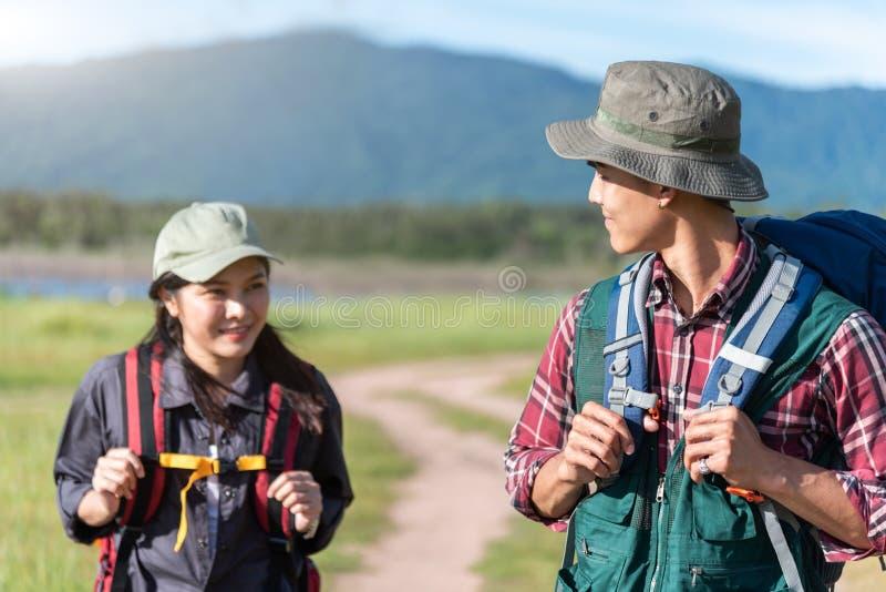 Δύο άνθρωποι που περπατούν στην πορεία στον τομέα λιβαδιών Αρσενικός και θηλυκός ταξιδιώτης που εξετάζει το σημείο άποψης έλξης Π στοκ φωτογραφία
