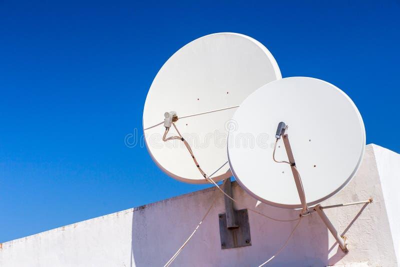 Δύο άσπρα δορυφορικά πιάτα στον τοίχο σπιτιών στοκ εικόνα