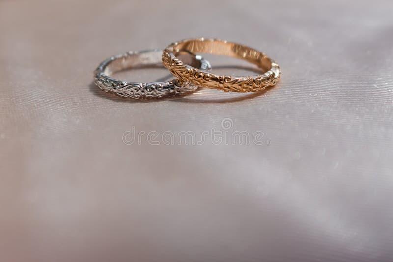 Δύο άσπρα και ρόδινα χρυσά γαμήλια δαχτυλίδια στο υπόβαθρο σατέν, έννοια γαμήλιων δαχτυλιδιών στοκ εικόνα