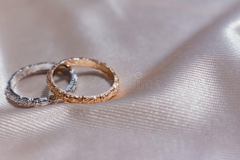 Δύο άσπρα και ρόδινα χρυσά γαμήλια δαχτυλίδια στο υπόβαθρο σατέν, έννοια γαμήλιων δαχτυλιδιών στοκ φωτογραφία με δικαίωμα ελεύθερης χρήσης