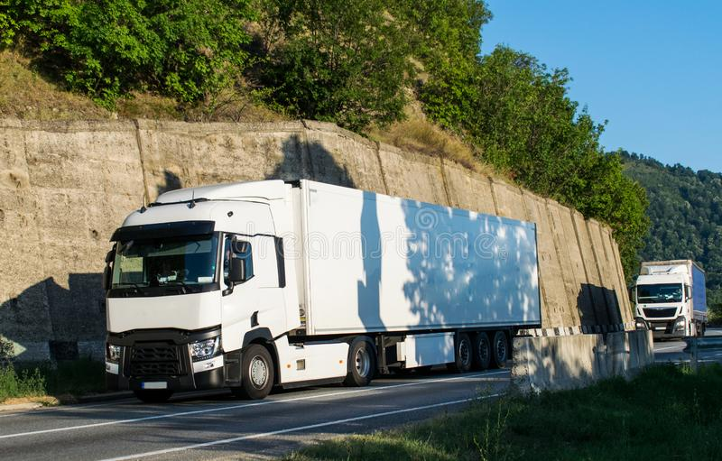 Δύο άσπρα φορτηγά που μεταφέρουν τα εμπορεύματα, που πηγαίνουν σε έναν όμορφο δρόμο κοντά στο βουνό στοκ εικόνες