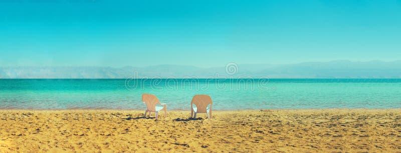 Δύο άσπρες καρέκλες παραλιών στην παραλία διάστημα αντιγράφων Έννοια καλοκαιριού, διακοπών και ταξιδιού απαγορευμένα στοκ εικόνες