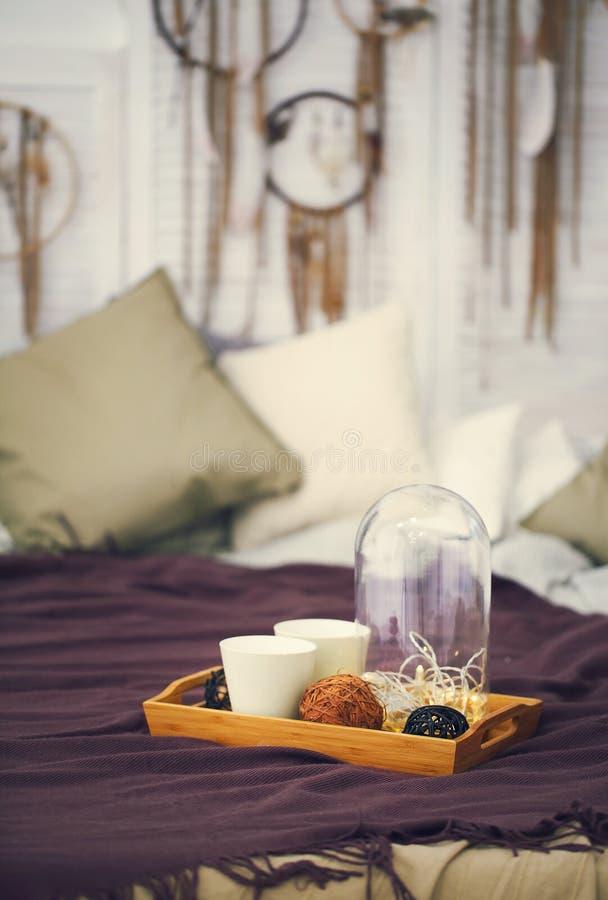 Δύο άσπρες κούπες σε έναν δίσκο στο κρεβάτι στο ύφος boho στοκ εικόνες