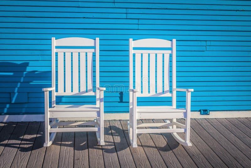 Δύο άσπρες υπαίθριες ξύλινες καρέκλες ενάντια στον μπλε τοίχο στοκ φωτογραφίες με δικαίωμα ελεύθερης χρήσης