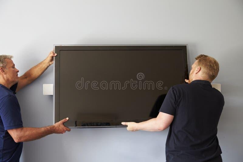 Δύο άτομα που εγκαθιστούν την επίπεδη τηλεόραση οθόνης στον τοίχο στοκ φωτογραφία