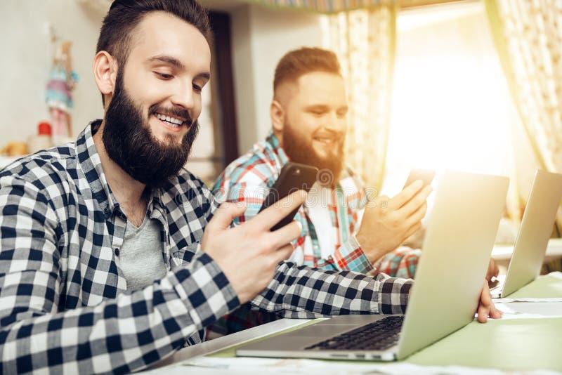 Δύο άτομα που κάθονται σε έναν καφέ εξετάζουν τα κινητά τηλέφωνα στοκ εικόνες με δικαίωμα ελεύθερης χρήσης