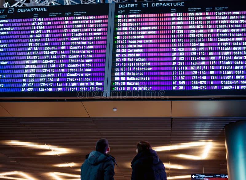 Δύο άτομα που στέκονται στο πρόγραμμα των πτήσεων στον αερολιμένα της Μόσχας Vnukovo στοκ φωτογραφία