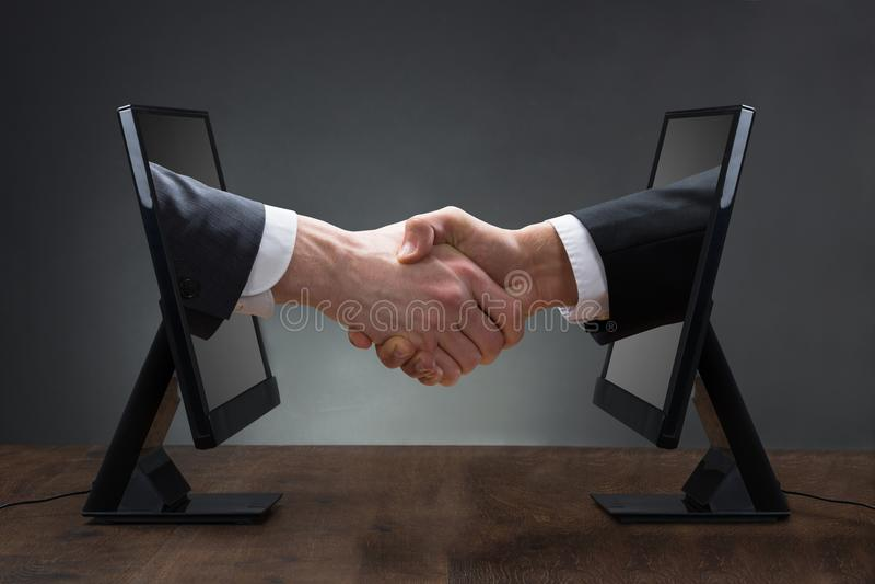 Δύο άτομα που τινάζουν τα χέρια που προέρχονται από τον υπολογιστή στοκ φωτογραφίες με δικαίωμα ελεύθερης χρήσης