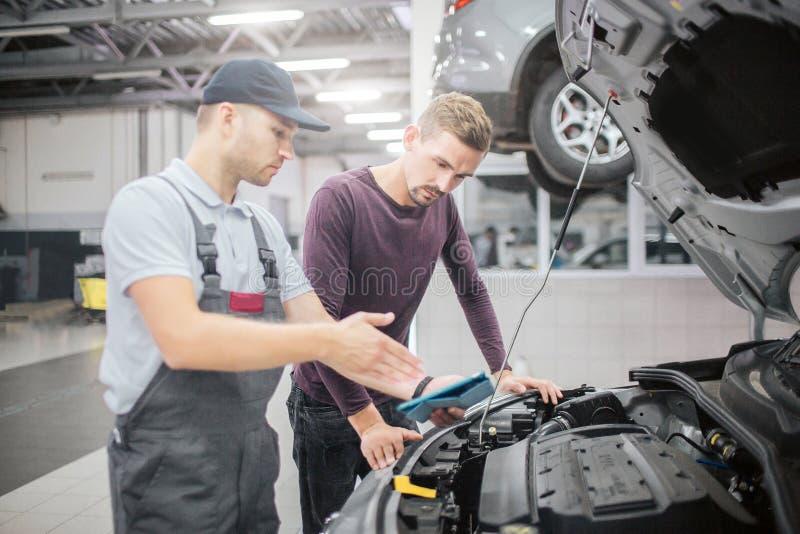 Δύο άτομα στέκονται στο ανοιγμένο μπροστινό μέρος του σώματος αυτοκινήτων Σημείο εργαζομένων σε το Έχουν τη συνομιλία Γενειοφόρο  στοκ φωτογραφίες με δικαίωμα ελεύθερης χρήσης