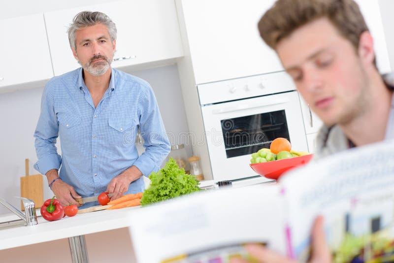 Δύο άτομα στην κουζίνα ένα που προετοιμάζουν τα λαχανικά άλλη ανάγνωση από τη συνταγή κρατούν στοκ φωτογραφίες με δικαίωμα ελεύθερης χρήσης