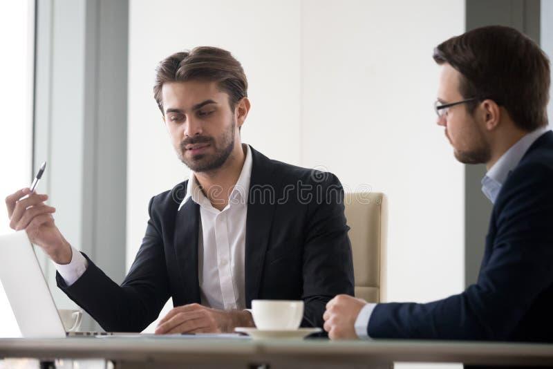 Δύο άτομα συζητούν το επιχειρησιακό πρόγραμμα εξετάζοντας την οθόνη lap-top στοκ φωτογραφία με δικαίωμα ελεύθερης χρήσης