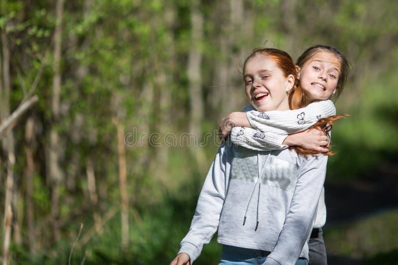 Δύο αγκαλιάσματα φίλων κοριτσιών εφήβων αδελφών και κατοχή της διασκέδασης στο πάρκο στοκ φωτογραφία