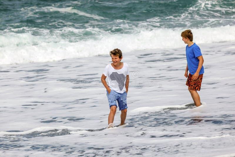 Δύο αγόρια εφήβων έχουν τη διασκέδαση στην παραλία στοκ εικόνα