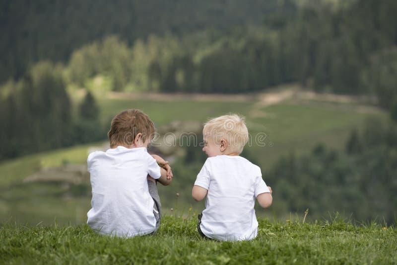 Δύο αγόρια κάθονται σε έναν λόφο και έχουν τη διασκέδαση υποστηρίξτε την όψη στοκ εικόνες