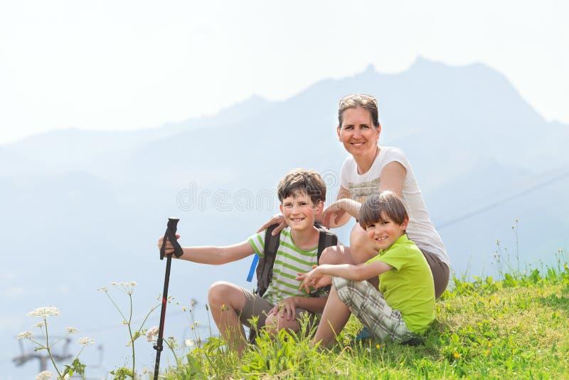 Δύο αγόρια με τη μητέρα κάθονται σε μια κορυφή του βουνού στοκ φωτογραφία με δικαίωμα ελεύθερης χρήσης