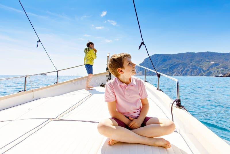 Δύο αγόρια παιδάκι, απόλαυση καλύτερων φίλων που πλέουν το ταξίδι βαρκών Οικογενειακές διακοπές στον ωκεανό ή τη θάλασσα την ηλιό στοκ εικόνα με δικαίωμα ελεύθερης χρήσης