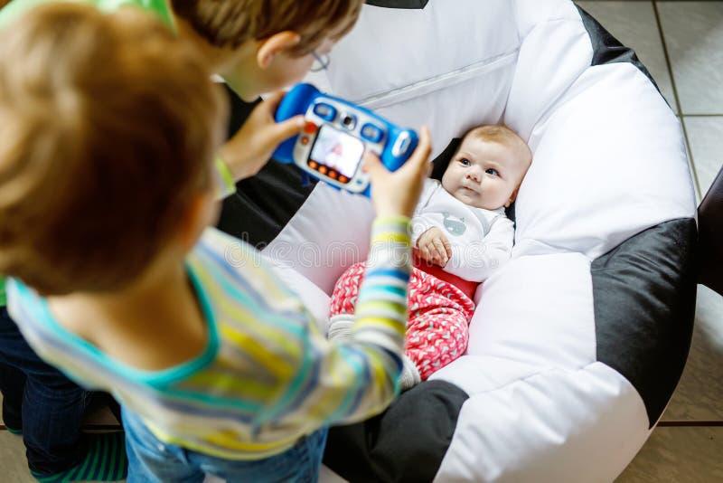 Δύο αγόρια παιδιών αμφιθαλών που παίρνουν την εικόνα με τη κάμερα παιχνιδιών του χαριτωμένου κοριτσάκι στοκ φωτογραφίες