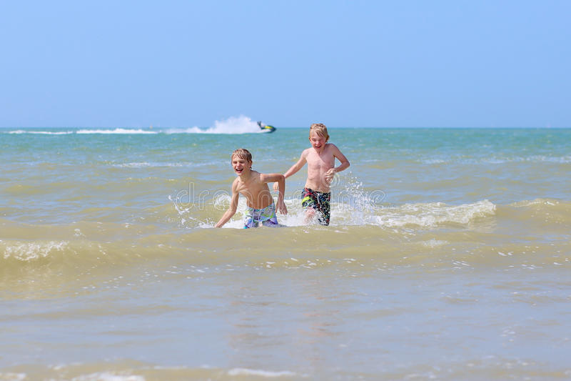 Δύο αγόρια που έχουν τη διασκέδαση στη θάλασσα στοκ φωτογραφίες