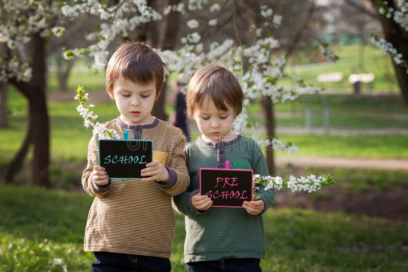 Δύο αγόρια, που κρατούν τους πίνακες με τα σημάδια στοκ φωτογραφίες