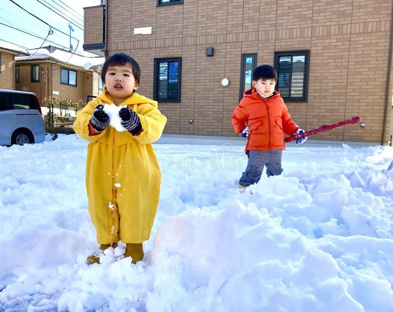 Δύο αγόρια που παίζουν το χιόνι στο έδαφος χιονιού στοκ εικόνες με δικαίωμα ελεύθερης χρήσης