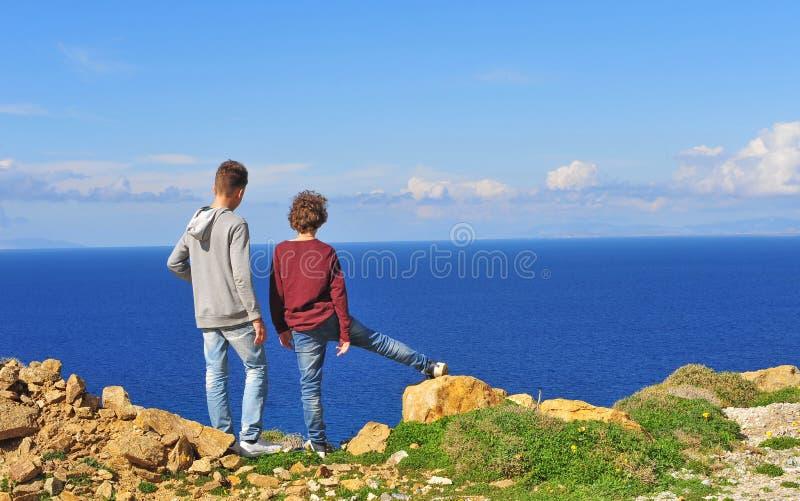 Δύο αγόρια που στέκονται στους απότομους βράχους θαλασσίως στοκ εικόνα
