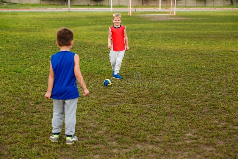 Δύο αγόρια στο ομοιόμορφο παίζοντας ποδόσφαιρο στην πράσινη χλόη στοκ εικόνα