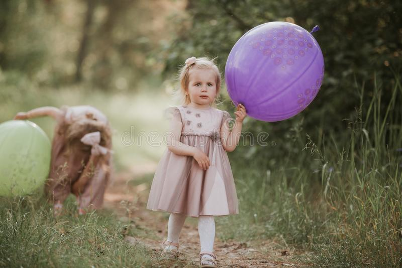 Δύο αδελφές παίζουν τα μπαλόνια κατσίκια που παίζουν από κοινού Ευτυχής αδελφή με τα μπαλόνια που περπατά στον τομέα άνοιξη στοκ εικόνες