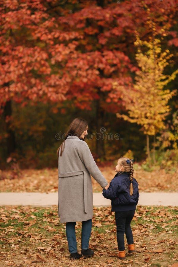 Δύο αδελφές περπατούν στο πάρκο στο χρόνο φθινοπώρου Παιδική ηλικία εποχή και έννοια-ευτυχής οικογένεια ανθρώπων στοκ φωτογραφίες