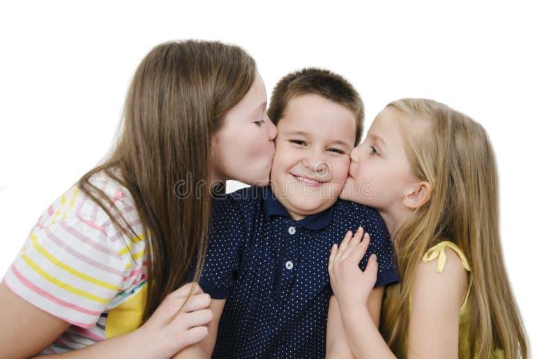 Δύο αδελφές που φιλούν τον έκπληκτο αδελφό Δύο νέα κορίτσια που φιλούν το έκπληκτο μικρό παιδί στοκ φωτογραφίες