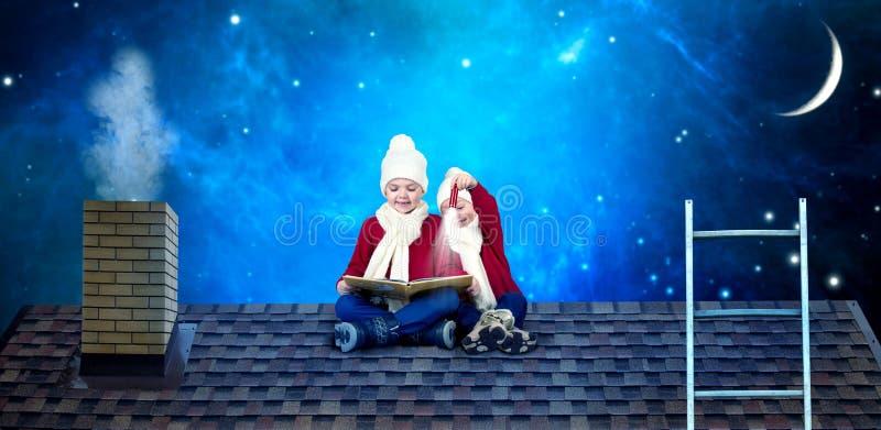 Δύο αδελφοί κάθονται στη νύχτα Χριστουγέννων στη στέγη και διαβάζουν ένα βιβλίο με τα παραμύθια Σε αναμονή για τα θαύματα Χριστου στοκ εικόνες με δικαίωμα ελεύθερης χρήσης