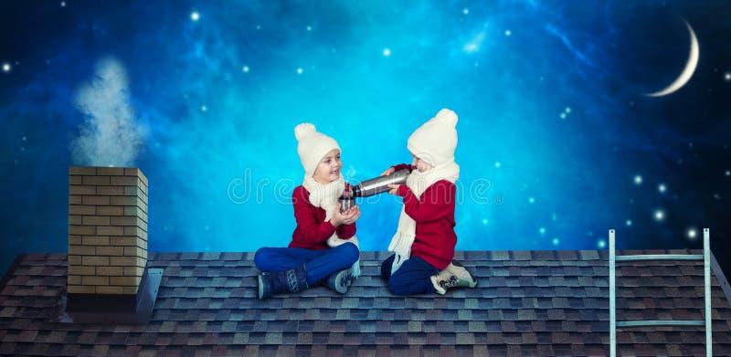Δύο αδελφοί κάθονται στη νύχτα Χριστουγέννων στο καυτό τσάι στεγών και ποτών από ένα μπουκάλι thermos Χαρούμενα Χριστούγεννα και  στοκ εικόνα