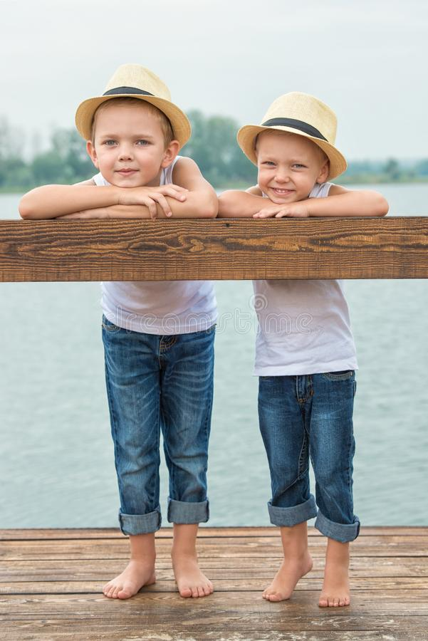 Δύο αδελφοί στηρίζονται στη λίμνη και τον περίπατο στην αποβάθρα στοκ εικόνα με δικαίωμα ελεύθερης χρήσης