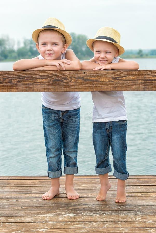 Δύο αδελφοί στηρίζονται στη λίμνη και τον περίπατο στην αποβάθρα στοκ εικόνες