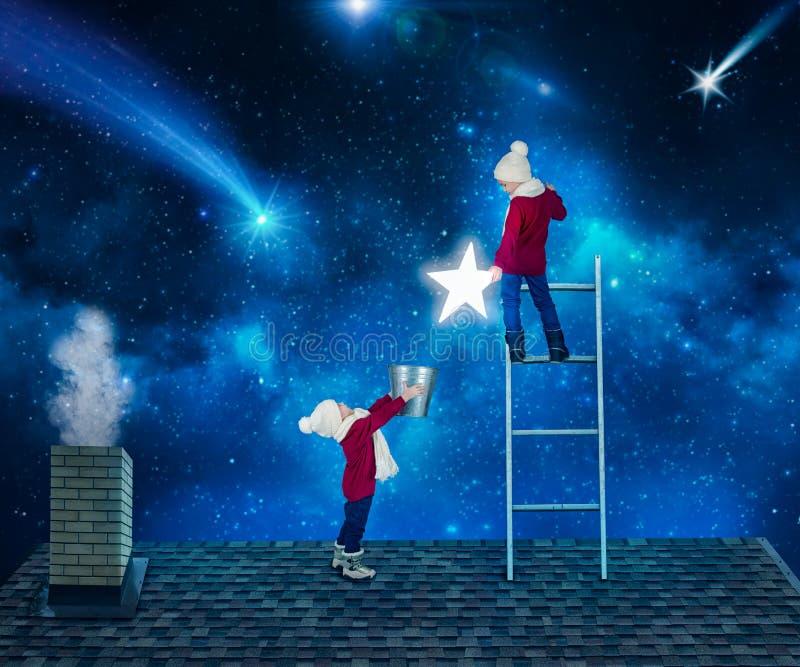 Δύο αδελφοί στη νύχτα Χριστουγέννων που στέκεται στη στέγη του σπιτιού και συλλέγουν τα αστέρια από τον ουρανό σε έναν κάδο Χριστ στοκ εικόνες