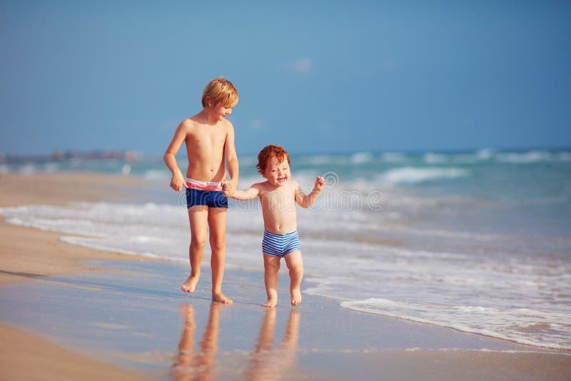 Δύο αδελφοί, χαριτωμένα παιδιά που έχουν τη διασκέδαση στην αμμώδη παραλία στοκ φωτογραφίες με δικαίωμα ελεύθερης χρήσης