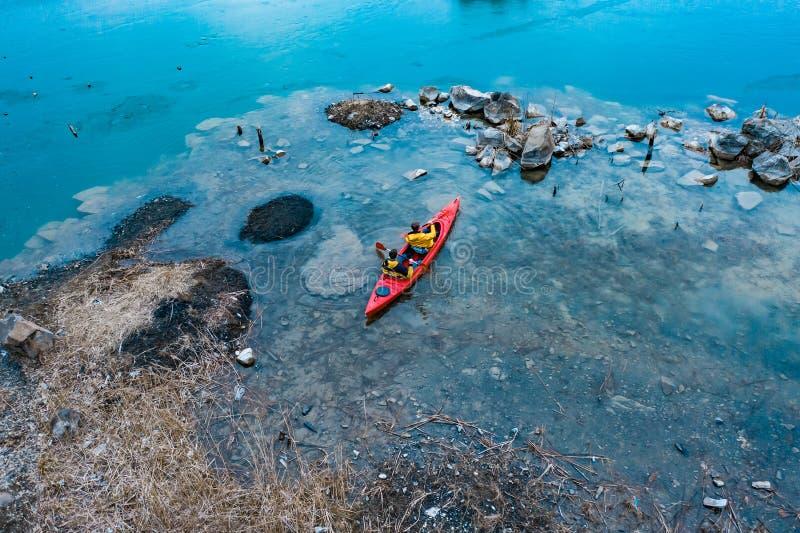 Δύο αθλητικά επιπλέοντα σώματα ατόμων σε μια κόκκινη βάρκα στον ποταμό στοκ εικόνες