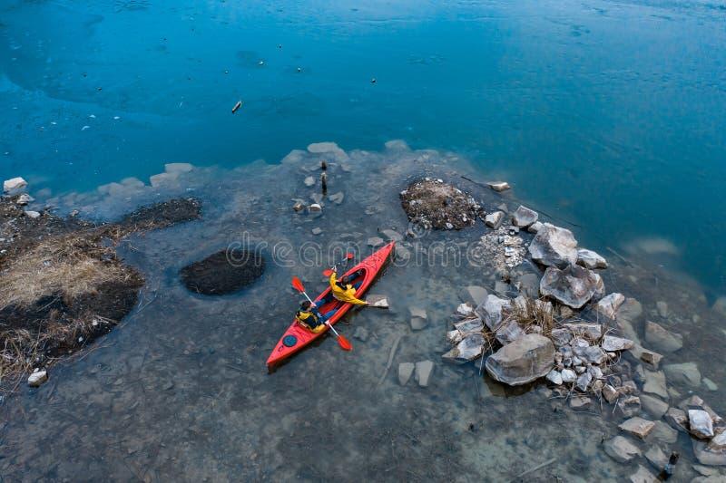 Δύο αθλητικά επιπλέοντα σώματα ατόμων σε μια κόκκινη βάρκα στον ποταμό στοκ φωτογραφία