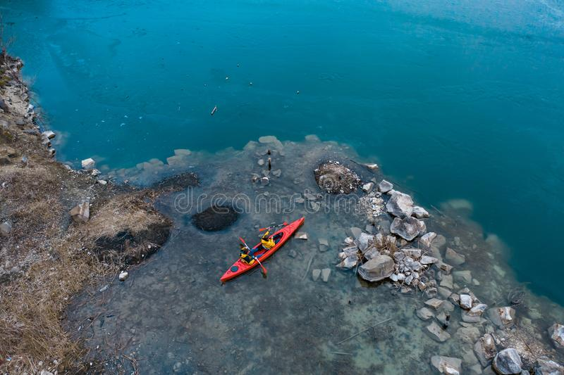 Δύο αθλητικά επιπλέοντα σώματα ατόμων σε μια κόκκινη βάρκα στον ποταμό στοκ εικόνα με δικαίωμα ελεύθερης χρήσης