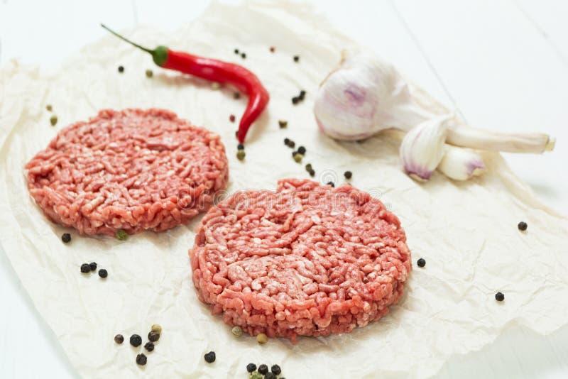 Δύο ακατέργαστα χάμπουργκερ έκαναν από το οργανικό κρέας σε ένα άσπρο ξύλινο υπόβαθρο με τα καρυκεύματα στοκ φωτογραφίες