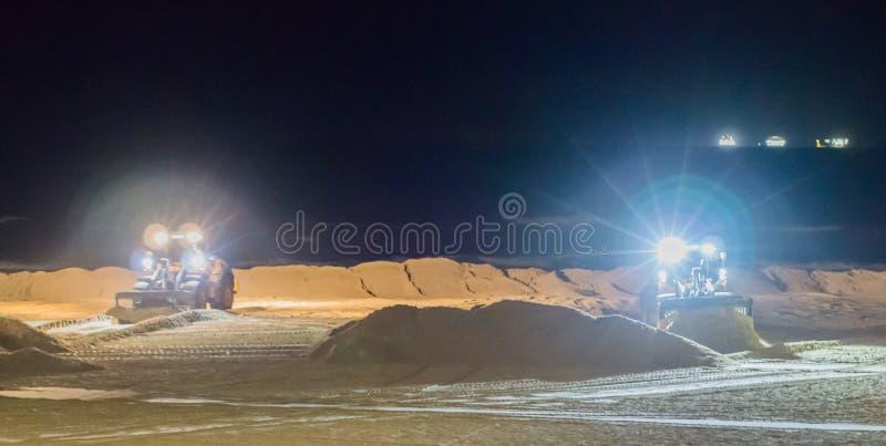 Δύο αλεσμένοι εργαζόμενοι που εργάζονται τη νύχτα στους εκσακαφείς στην παραλία που κινεί την άμμο στοκ φωτογραφίες με δικαίωμα ελεύθερης χρήσης