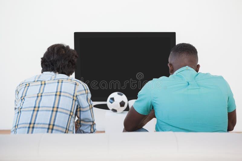 Δύο ανεμιστήρες ποδοσφαίρου που προσέχουν τη TV στοκ εικόνα