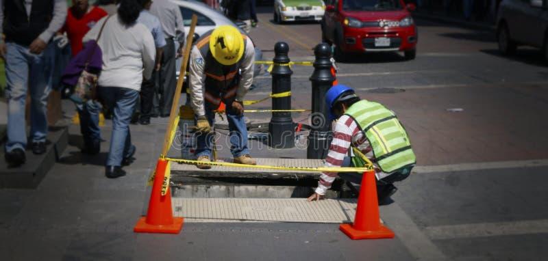 Δύο ανθρώπων εργασία στα ηλεκτρικά καλώδια υπογείων στοκ φωτογραφία με δικαίωμα ελεύθερης χρήσης