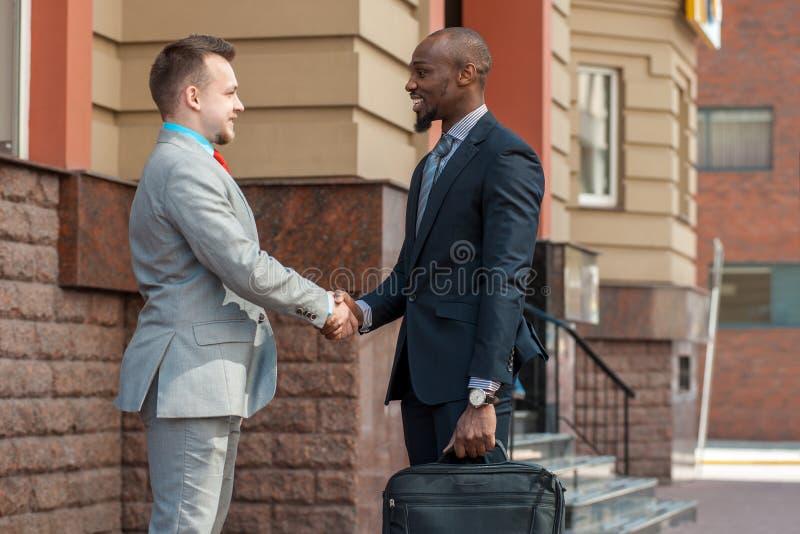 Δύο ανθρώπων στα κοστούμια που τινάζουν τα χέρια και το χαμόγελο υπαίθρια στοκ εικόνα
